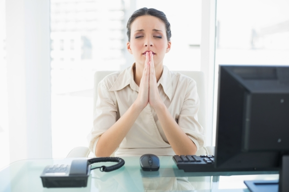 Anxious stylish brunette businesswoman praying in bright office
